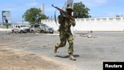 FILE - Somali government soldier runs to take position in front of the Parliament during fighting between them and al-Shabab militia in the capital Mogadishu, May 24, 2014.