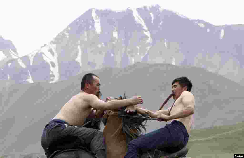 Participants wrestle while riding horses during the Kyrgyz national horse games and festival near the Tulpar-Kul lake in the Chon Alai mountain range, some 3500 meters (11483 feet) above sea level, in the Osh region of Kyrgyzstan, July 25, 2015.