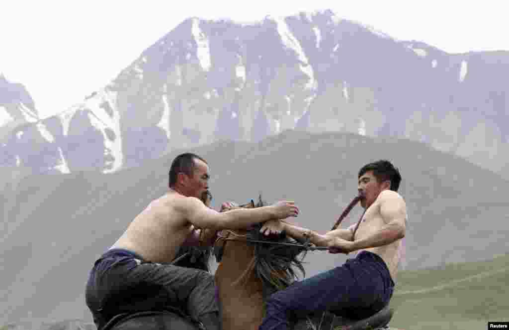 Dua peserta bergulat sambil mengendarai kuda mereka dalam lomba olahraga tradisional di wilayah pegunungan Osh di Kyrgyzstan.