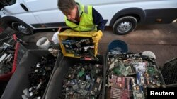 FILE - Samo Oblak sorts out computer parts at a dump yard in Kranj, Slovenia.