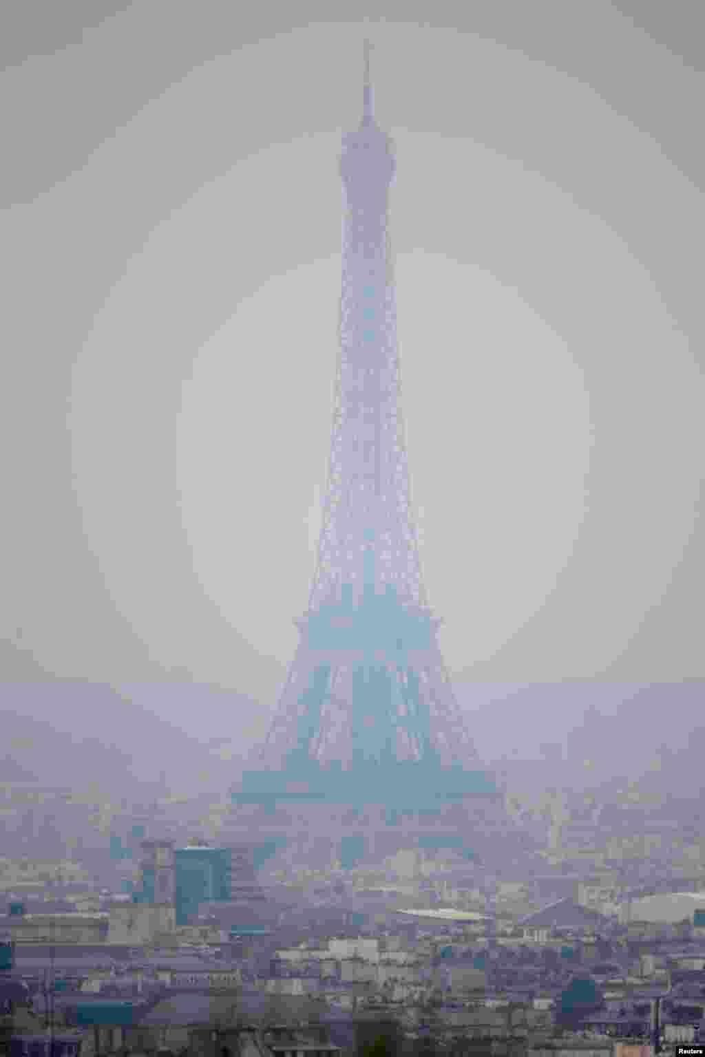 Kabut asap atau smog yang menyelimuti menara Eiffel dan kota Paris (17/3) mendorong pemerintah memberlakukan aturan yang membatasi jumlah kendaraan di jalan ibukota dan pinggiran kota. (Reuters/Charles Platiau)