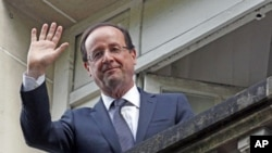 France's newly-elected President Francois Hollande waves from a balcony at his campaign headquarters the day after his election, in Paris, May 7, 2012.