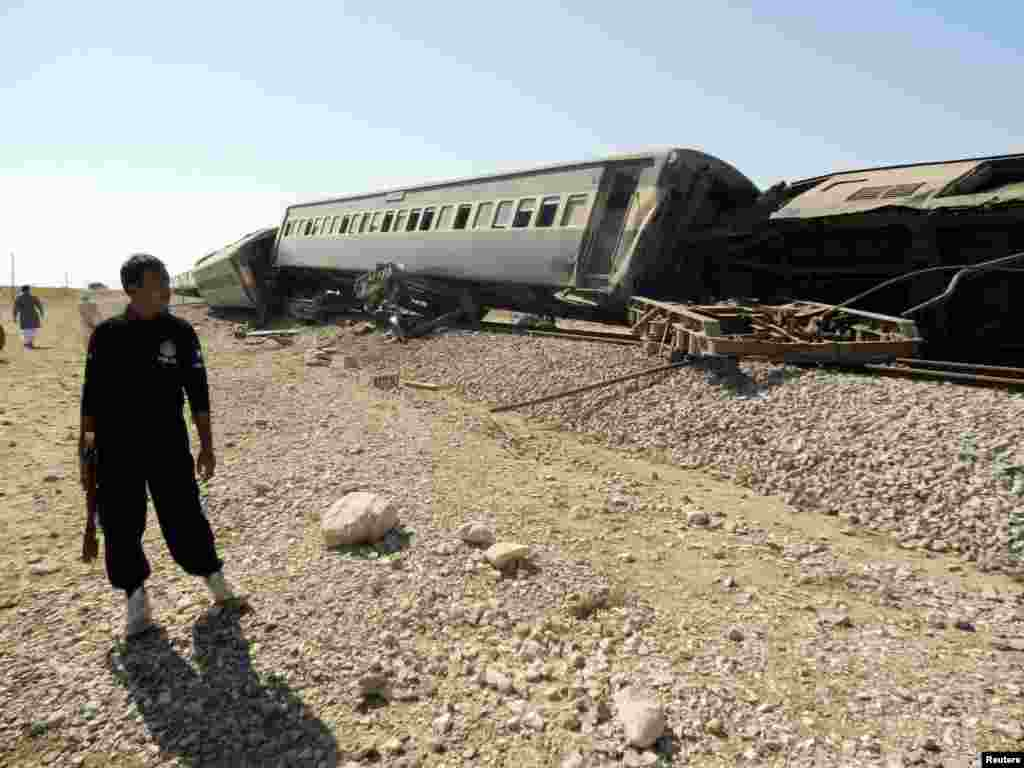 A security official stands near a passenger train that derailed after it was hit by a bomb attack in Baluchistan province, Pakistan, Oct. 21, 2013.