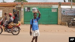 A boy selling soft drinks walk past a clinic taking care of Ebola patients in the Kenema District on the outskirts of Kenema, Sierra Leone, July 27, 2014.