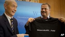 Pascal Lamy, left, Director-General of the World Trade Organization (WTO) hands over a t-shirt with a logo saying ' Welcome to the WTO...finally!' to Maxim Medvedkov, the Chief WTO negotiator for the Russian Federation in Geneva, Switzerland, November 10,