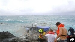 People clamber on the rocky shore on Christmas Island during a rescue attempt as a boat breaks up in the background, 15 Dec 2010