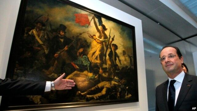 """Presiden Perancis Francois Hollande di depan lukisan Eugene Delacroix  yang berjudul """"Liberty Leading the People"""" yang dicoret oleh pengunjung hari Kamis, 7/2 (foto: dok)."""