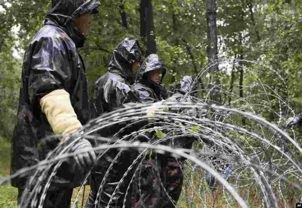 Hungarian soldiers put up spools of razor wire on Slovenian border in Zitkovci. Hungary has installed spools of razor wire near a border crossing with Slovenia, which like Hungary is part of the EU's Schengen zone of passport-free travel.
