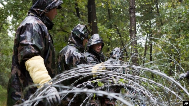 FILE - Hungarian soldiers put up spools of razor wire on Slovenian border in Zitkovci, Sept. 25, 2015. Hungary installed spools of razor wire near a border crossing with Slovenia, which like Hungary is part of the EU's Schengen zone of passport-free travel.