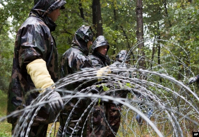 Hungarian soldiers put up spools of razor wire on Slovenian border in Zitkovci, Sept. 25, 2015. Hungary has installed spools of razor wire near a border crossing with Slovenia, which like Hungary is part of the EU's Schengen zone of passport-free travel.