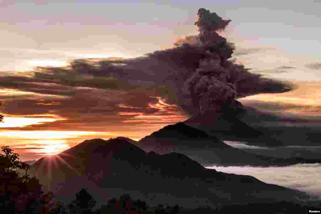 Mount Agung volcano is seen spewing smoke and ash in Bali, Indonesia, in this picture obtained from social media.