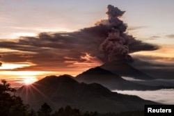 Mount Agung volcano is seen spewing smoke and ash in Bali, Indonesia, November 26, 2017 in this picture obtained from social media.