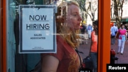 FILE - A woman walks past a 'Now Hiring' sign as she leaves the Urban Outfitters store at Quincy Market in Boston, Massachusetts.