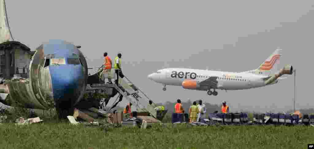 Un avión de pasajeros aterriza mientras trabajadores desmantelan un avión abandonado en el aeropuerto internacional Murtala Muhammed en Lagos, Nigeria.