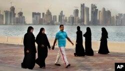 Tư liệu - Người dân đi bộ bên cạnh biển với những tòa nhà chọc trời đằng sau, ở Doha, Qatar, ngày 7 tháng 4, 2012.