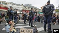 Lính Pháp đứng gần một người biểu tình phản đối toàn cầu hóa và vấn đề thuế tại biên giới Pháp-Monaco