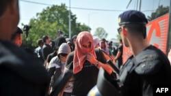 Hrvatska policija posmatra migrante koji su ukrcavaju u autobus blizu granice Hrvatske i Srbije