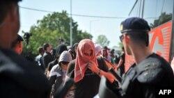 17일 크로아티아와 세르비아 국경 지역 난민들이 크로아티아 경찰의 감독을 받으며 버스에 올라타고 있다.