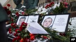 Foto seorang Pilot Rusia yang tewas setelah pesawatnya ditembak Turki, Letkol. Oleg Peshkov (kiri) -- dan foto pelaut Alexander Pozynich (kanan) ditempatkan pada sebuah monumen di kantor militer Rusia di Moskow (26/11).