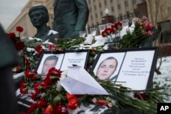 FILE - Photos of Lt.Col. Oleg Peshkov, left, and sailor Alexander Pozynich are placed at a monument to Soviet Officers with flowers and a toy jet made of paper outside Russian Army General Staff headquarters in Moscow, Nov. 26, 2015.