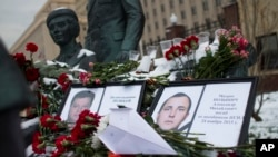 Photos of Lt.Col. Oleg Peshkov, left, and sailor Alexander Pozynich are placed at a monument to Soviet Officers with flowers and a toy jet made of paper outside Russian Army General Staff headquarters in Moscow, Nov. 26, 2015.