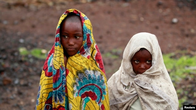 Girls, displaced by recent fighting between Congolese army and the M23 rebels, cover themselves from the cold in Munigi village near Goma in the eastern Democratic Republic of Congo, Sept. 1, 2013.