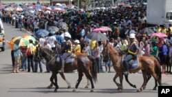 Police on horseback ride past people waiting to view the body of former South African president Nelson Mandela in Pretoria South Africa, Dec. 11, 2013.