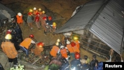 Firefighters rescue people from a house following a landslide in Chittagong, Bangladesh, June 26, 2012.