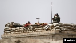 FILE - Fighters of the Syria Democratic Forces (SDF) are seen atop a fortified watch post near Raqqa, Syria, May 27, 2016. The U.S. has been supporting the SDF with weapons and airstrikes.