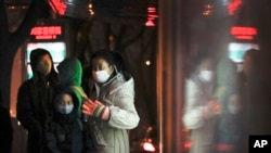 FILE - Commuters wearing protection masks, wait for buses at a bus station on a heavy polluted day in Beijing, China.