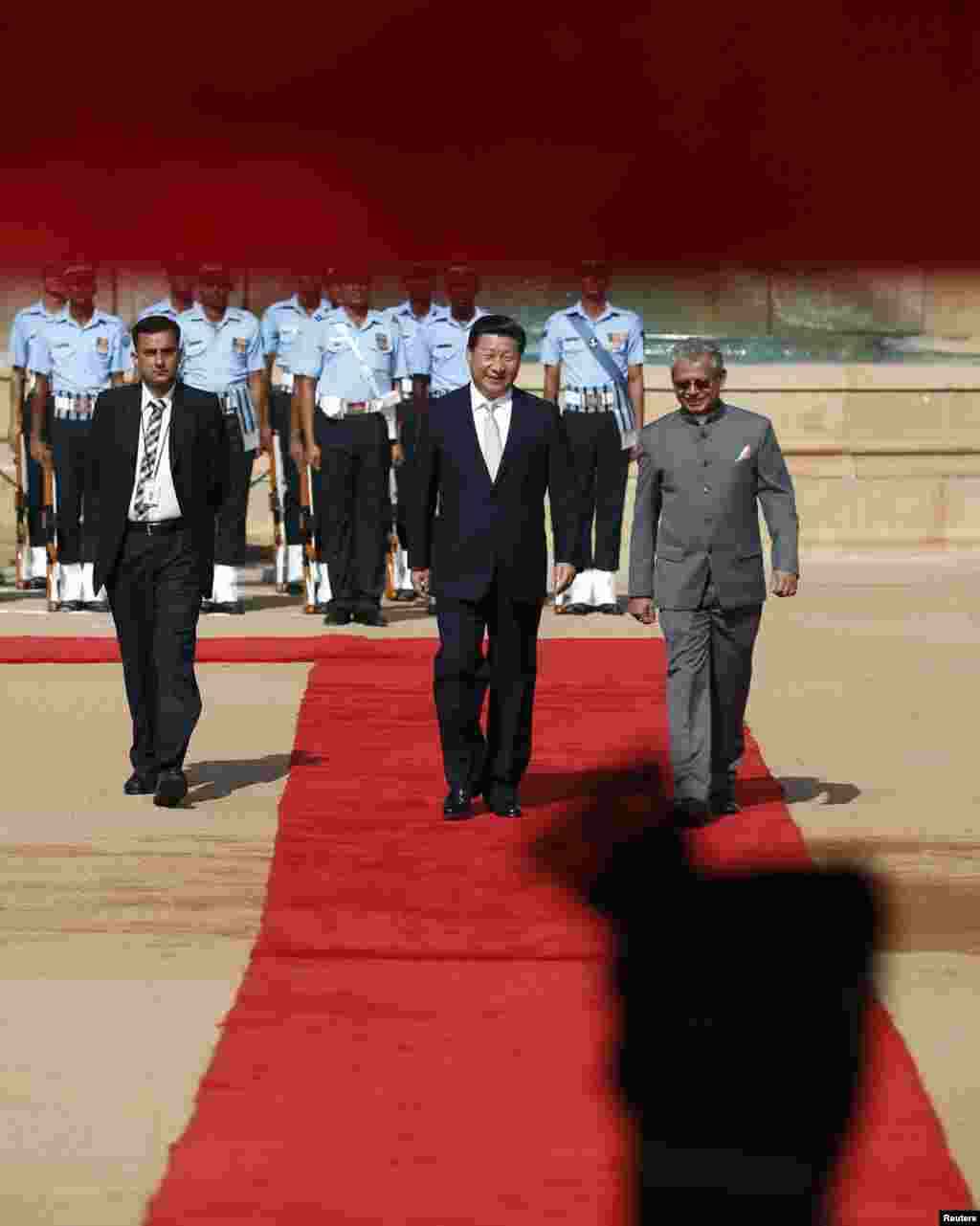 Chinese President Xi Jinping (center) walks on the red carpet after inspecting a guard of honor during his ceremonial reception at the forecourt of the Rashtrapati Bhavan presidential palace in New Delhi, Sept. 18, 2014.