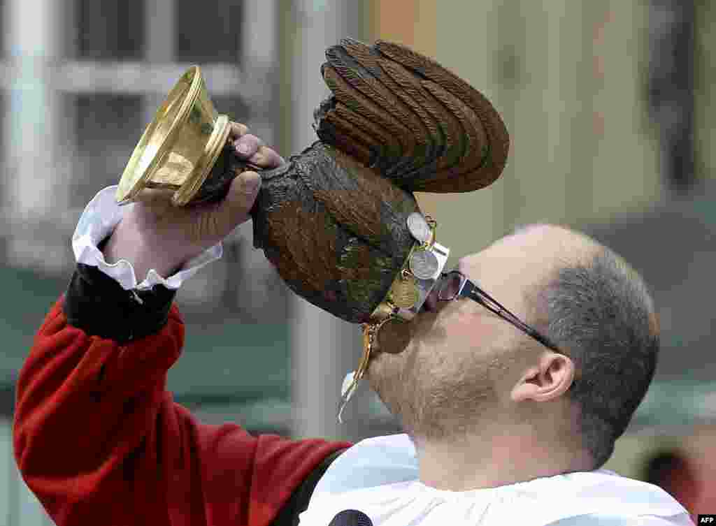 A man drinks from a wooden wine jug during the Salter Festival in Schwaebisch-Hall, southern Germany. The annual salter festival is held since the 14th century to celebrate the salt production that promoted the city of Schwaebisch-Hall.