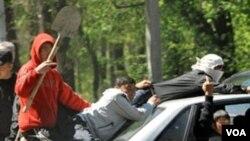 Kelompok etnis Kyrgyz tampak mengendarai mobil di ibukota Bishkek dengan bersenjata pentungan, 19 April 2010.
