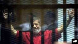 ອະດີດປະທານາທິບໍດີຂອງອີຈິບ ທ່ານ Mohammed Morsi, ໃສ່ສຸດສີແດງຂອງພວກນັກໂທດ ທີ່ຖືກຕັດສິນປະຫານຊີວິດ, ຍົກມືສອງກ້ຳຂຶ້ນ ຢູ່ໃນຫ້ອງຄຸມຂັງຊົ່ວຄາວຂອງສານ ຢູ່ກົມຕຳຫຼວດແຫ່ງຊາດ ທາງພາກຕາເວັນອອກ ຂອງ ນະຄອນຫຼວງ Cairo.