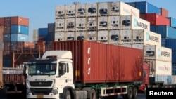 资料照片:一辆卡车运载着集装箱行驶在天津港附近一处物流中心。(2019年12月12日)