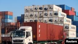 中國天津,一名工人在天津港附近的一個物流中心駕駛一輛載有貨櫃箱的貨車(2019年12月12日)。