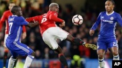 Paul Pogba de Manchester United tente une aile de pigeon au milieu de N'Golo Kante, à gauche, et Willian, à droite, de Chelsea au cours d'un match du championnat anglais, entre Chelsea et Manchester United au stade à Londres, le 13 mars 2017.