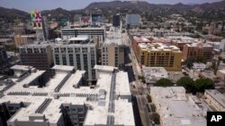 FILE - Apartment buildings line the streets in Los Angeles, July 30, 2018. Millennials are rejecting larger, expensive metropolises for smaller cities that offer more affordable housing and a lower other cost of living, according to a new report.