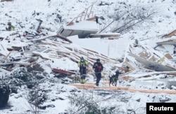 Rumah-rumah yang rata dengan tanah nampak diselimuti salju, saat Tim SAR dan seekor anjing penyelamat melakukan pencarian korban di daerah longsor di Ask, Gjerdrum, Norwegia 2 Januari 2021. (NTB / Erik Schroeder via REUTERS)