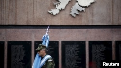 FILE - Argentine Falkland War veteran Jose Gonzalez pays homage to Argentine soldiers who died in the 1982 conflict between Britain and Argentina in the Falkland Islands, known to Argentines as 'Malvinas' at the memorial dedicated to them in Buenos Aires, April 2, 2016.