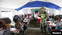 A border defense policeman teaches primary students protective measures in the event of an earthquake, at a temporary tent classroom, in Gyirong county, Tibet Autonomous Region, China, May 13, 2015.