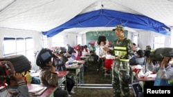 A border defense policeman teaches primary students protective measures in the event of an earthquake in Tibet. May 13, 2015.