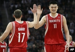 Houston Rockets Yao Ming (11) high fives teammate Brent Barry (17) during the fourth quarter of their NBA basketball game against the Cleveland Cavaliers in Ohio, Dec. 23, 2008 (Reuters).