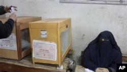 星期三一位埃及候選人的代表,獲委任為監察投票,在埃及吉薩投票中心看管投票箱票。