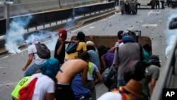 Los manifestantes lanzan piedras contra oficiales de la Policía Nacional Bolivariana durante una protesta en Caracas, Venezuela, el sábado 8 de abril de 2017.