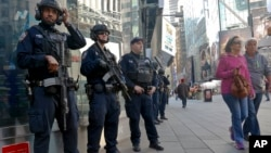 FILE - Officers from the New York Police Department's anti-terror unit patrol Times Square, Nov. 4, 2016.