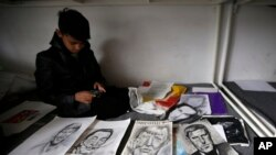 FILE - Farhad Nouri sits on a bed by portraits of Serbian tennis player Novak Djokovic, left, Spanish painter Salvador Dali, and German Chancellor Angela Merkel, third from left on March 13, 2017. (AP Photo/Darko Vojinovic)