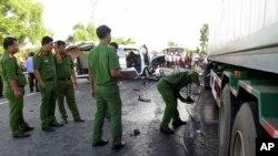 Cảnh sát xem xét hiện trường tai nạn sau khi xe khách chở gia đình chú rể đâm vào xe container ở Quảng Nam. (Do Van Truong/Vietnam News Agency via AP)