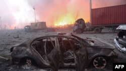 This photo taken on August 13, 2015 shows a destroyed car as a fire continues to burn after a series of explosions at a chemical warehouse hit the city of Tianjin, in northern China.
