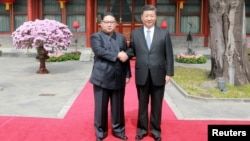 North Korean leader Kim Jong Un shakes hands with Chinese President Xi Jinping in Beijing, as he paid an unofficial visit to China, in this undated photo released by North Korea's Korean Central News Agency in Pyongyang, March 28,2018.